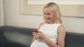 Dichte omhooggaand van een zwangere vrouwenzitting op de bank, holding een telefoon Zij bekijkt het scherm en glimlacht stock video
