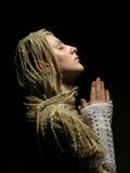 Dichte omhooggaand van het profiel van een jong biddend meisje stock foto