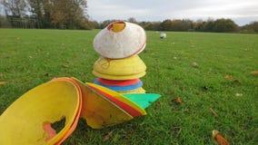Dichte omhooggaand van kegelstapel met voetballen op de achtergrond Royalty-vrije Stock Foto