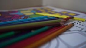 Dichte is omhooggaand van kleurenpotloden op de kleuring van de kinderen, langzame motie stock video