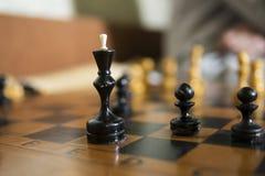 Dichte schaakraad geconcentreerd op zwart koning en pand Stock Foto