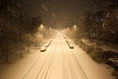Dichte Schneefälle und leere Straße nachts Stockbilder