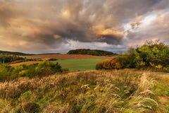 Dichte Wolken belichtet bis zum der Sonne und dem bunten Herbst Stockfoto