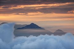 Dichte Wolkenschicht mit konischer Spitze und orange Morgennebel stockbild