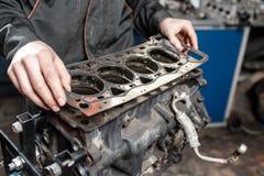 Dichtung in der Hand Der Mechaniker bauen Blockmaschinenfahrzeug auseinander Maschine auf einem Reparaturstand mit Kolben und lizenzfreie stockbilder