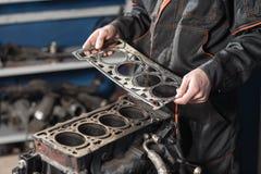 Dichtung in der Hand Der Mechaniker bauen Blockmaschinenfahrzeug auseinander Maschine auf einem Reparaturstand mit Kolben und stockbild