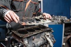 Dichtung in der Hand Der Mechaniker bauen Blockmaschinenfahrzeug auseinander Maschine auf einem Reparaturstand mit Kolben und lizenzfreie stockfotos