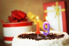 Diciannove anni di compleanno Dolce con la candela bruciante ed i regali immagine stock libera da diritti