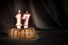 Diciassette anni di anniversario Dolce di cioccolato di compleanno con le candele brucianti bianche sotto forma di numero diciass fotografia stock