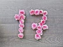 17, diciassette - numero d'annata delle rose rosa sui precedenti di legno scuro fotografia stock libera da diritti
