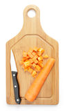 Dicing carrots. On a chopping board with a knife royalty free stock photo