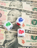 Dicing with the currency: American Dollar. Three dice on top of United States ten Dollar bills. There are risks with quantitative easing [ printing money ] and Stock Images