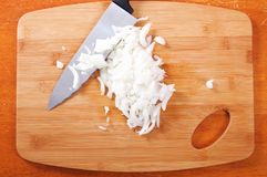 Dicing Onions on a cutting board. Close up with hands royalty free stock photo