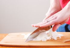 Dicing Onions on a cutting board. Close up with hands stock images