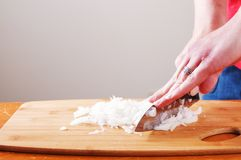 Dicing Onions on a cutting board. Close up with hands stock image