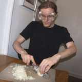 Dicing onions wearing goggles. Young man dicing onions wearing goggles royalty free stock images