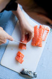 Dicing salmon. A chef dicing a piece of salmon in preparation for cooking stock photo