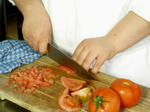 Dicing tomatoes. Chef is dicing tomatoes on the cutting board royalty free stock photography