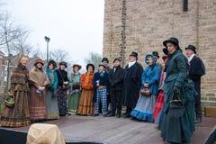 Dickens festiwalu kolęda ludzie śpiewają w ulicie przy kościół Obraz Royalty Free