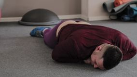 Dicker Mann, der auf dem Boden in der Turnhalle nach Übung liegt stock video footage