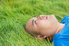 Dicker Mann, der auf dem grünen Gras mit Gedanken eines Druckes liegt Lizenzfreies Stockbild