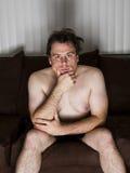 Dicker Mann, der auf der Couch denkt lizenzfreies stockbild