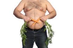 Dicker Mann, der Karotte hält Stockbilder