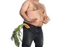 Dicker Mann, der Karotte hält Stockbild