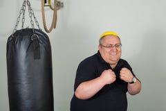 Dicker Mann, der mit einem Sandsack kämpft Lizenzfreie Stockfotos