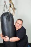 Dicker Mann, der mit einem Sandsack kämpft Stockbilder