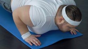 Dicker Mann, der unten auf die Yogamatte versucht, Plankenübung, Mangel zu tun an Energie fällt stock footage