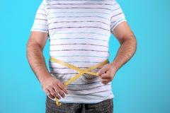 Dicker Mann mit messendem Band auf Farbhintergrund, Nahaufnahme stockbilder