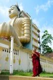 Dickwella,斯里兰卡, 04-15-2017 :和尚在佛教寺庙的手上拿着手机在菩萨雕象背景的  库存图片