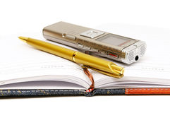 Dictaphone, notepad and ballpen. On white background Royalty Free Stock Image