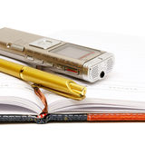 Dictaphone, notepad and ballpen. On white background Royalty Free Stock Photography