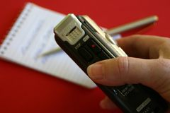 Dictation Notes. Hand holding dictaphone recorder with note pad and pen Stock Image