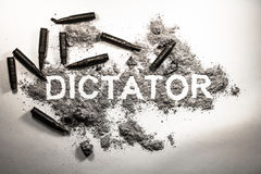 Dictator word written in  ash, dirt, dust with bullets around as Stock Image