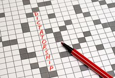 Dictatorship. Text in crossword. Red letters. Close-up royalty free stock photos