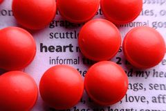 Dictionary definition of the word heart with medicin and pills.  Stock Images