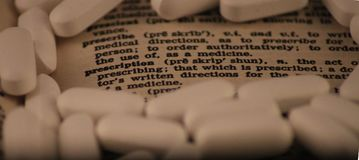 Dictionary entry for prescribe and prescription surrounded by white pills. A image of the dictionary entries for prescribe and prescription and their meanings Stock Photo