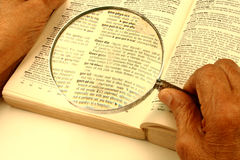 Dictionary and magnifier. Searching words in a dictionary through a magnifier Royalty Free Stock Images