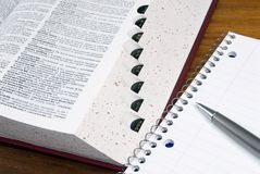 Dictionary and notebook. An open dictionary with a notebook and pen Stock Photography