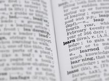 Dictionary page featuring definition of the word learn with selective focus applied. This photograph features a page from a vintage 1964 dictionary featuring the royalty free stock photos