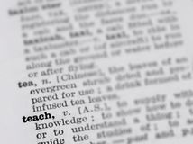 Dictionary page featuring definition of the word teach with selective focus applied. This photograph features a page from a vintage 1964 dictionary featuring the royalty free stock images