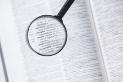 Dictionary page viewed through magnifying glass Royalty Free Stock Photos