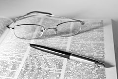 Dictionary with a pair of glasses and pen Royalty Free Stock Photography