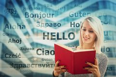 Dictionary. Student girl holding a dictionary and word hello translated in different languages on the background. Young school teacher learning and speaking many Royalty Free Stock Images