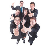 We did it!. Young group of business people showing thumbs up signs in joy Royalty Free Stock Photography