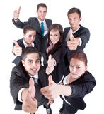 We did it!. Young group of business people showing thumbs up signs in joy Royalty Free Stock Images