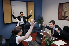 We Did It!. Team of three work colleagues with their arms raised in celebration Stock Image